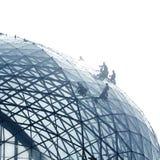 Arbeitskräfte, die eine runde Glasfassade säubern Stockbild