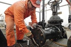Arbeitskräfte, die für das Laden des Rohöls sich vorbereiten Stockfoto