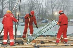 Arbeitskräfte, die Glasfenster auf Gebäude einbauen stockbild