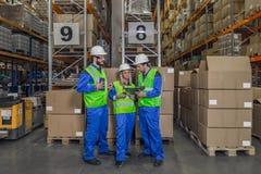 Arbeitskräfte, die Klemmbrett betrachtend stehen Stockfoto