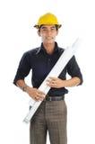 Arbeitskräfte, die Sicherheitssturzhelm-Holdingzeichnungsplan tragen Stockfotos