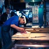 Arbeitskräfte, die Thunfisch am Tsukiji Markt in Japan aufbereiten Lizenzfreie Stockfotografie