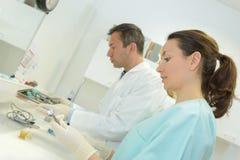 Arbeitskräfte, die zahnmedizinische Ausrüstung vorbereiten lizenzfreie stockfotografie