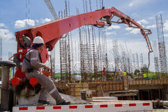 Arbeitskräfte, die Zement an einem Bau ausladen Lizenzfreies Stockbild