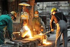 Arbeitskräfte in einer Gießerei, die ein Metallwerkstück - Sicherheit am Arbeitsplatz und Teamwork wirft stockfotografie
