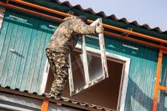 Arbeitskräfte entfernen das alte Fenster im Haus Stockfotografie