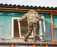 Arbeitskräfte entfernen das alte Fenster im Haus Lizenzfreies Stockbild