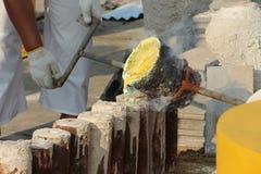 Arbeitskräfte gießen Gold in die Form, um eine Buddha-Statue herzustellen Lizenzfreie Stockfotos