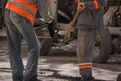 Arbeitskräfte gießen HarzStraßendecke, um den Asphalt zu bedecken Lizenzfreie Stockfotografie