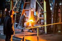 Arbeitskräfte halten das Werkstück unter dem Hammer Stockfoto