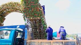 Arbeitskräfte konstruieren hoher Turm-Blumenbeet mit Blumentöpfen stock footage
