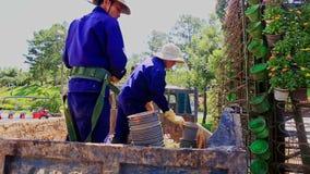Arbeitskräfte konstruieren hoher Turm-Blumenbeet mit Blumentöpfen stock video