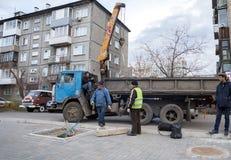 Arbeitskräfte nehmen an dem Pflanzen eines Baums teil, geholt mit dem LKW, in einem Wohngebiet lizenzfreie stockfotos