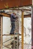 Arbeitskräfte reparieren die Fassade des Gebäudes Stockfotos