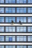 Arbeitskräfte säubern die Fenster auf den Wolkenkratzern stockfotografie