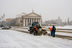 Arbeitskräfte säubern Schnee im Quadrat Stockfotografie