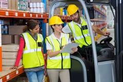 Arbeitskräfte schauen ein Klemmbrett Stockfoto