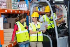 Arbeitskräfte schauen ein Klemmbrett Lizenzfreies Stockbild