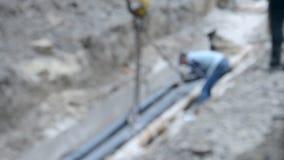 Arbeitskräfte setzten Rohre mit einem Baukran stock video footage