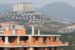 Arbeitskräfte sind auf einem Hintergrund des Hotels im Bau Stockbilder
