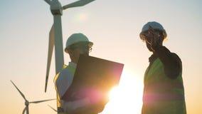 Arbeitskräfte sprechen auf einem Sonnenunterganghintergrund, Abschluss oben stock video footage