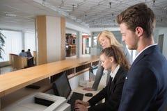 Arbeitskräfte und Manager, die Frage in der Hotelaufnahme lösen Lizenzfreies Stockfoto