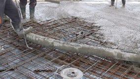 Arbeitskräfte verbreiten Beton über großem verstärktem Boden auf der Baustelle stock video