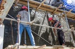 Arbeitskräfte vergipsen die Wand Stockfotos