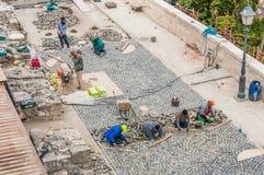 Arbeitskräfte, welche die Straße pflastert in Buda Castle errichten. Lizenzfreie Stockfotos