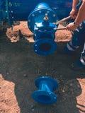Arbeitskraft übergibt schraubenden Schieber mit Nüssen auf Rohrleitung Lizenzfreies Stockfoto
