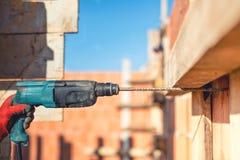 Arbeitskraft auf Baustelle unter Verwendung der Bohrmaschine und des Walzdrahts Stockfoto
