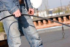 Arbeitskraft auf Dachholdingseilzug Stockfotos