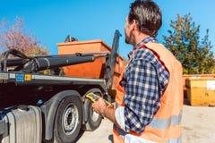 Arbeitskraft auf der Baustelle, die Behälter für Abfall vom LKW entlädt Lizenzfreie Stockfotografie