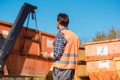 Arbeitskraft auf der Baustelle, die Behälter für Abfall von t entlädt Stockbild