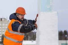 Arbeitskraft bedeckt die Gelenke von Eisplatten mit Nassschnee lizenzfreie stockfotos