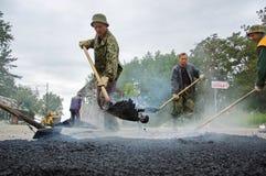 Arbeitskraft bei den asphaltierenarbeiten Stockfoto