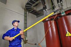 Arbeitskraft benutzt isolierenden Stock zur Erde, die Transformator erdet Stockfotografie