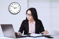 Arbeitskraft benutzt Laptop mit Uhr auf der Wand Lizenzfreies Stockbild
