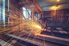 Arbeitskraft benutzt Winkelschleifer mit dem Brunnen von Funken in der Wohnung, die im Bau ist und gestaltet, Erneuerung um stockfotografie