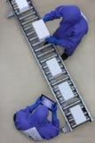 Arbeitskraft in der blauen Uniform, die mit Kästen auf Verpackungsfließband arbeitet lizenzfreies stockfoto