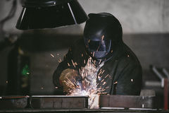 Arbeitskraft an der Fabrik im Sturzhelm ist vom Eisen in der schweißenden PR Stockbilder