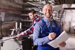 Arbeitskraft an der Fabrik mit Chef lizenzfreie stockfotografie