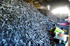 Arbeitskraft in der Holzkohlenfabrik Stockbild