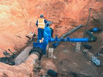 Arbeitskraft in der Sicherheitskleidung fahren Ventilrohr auf trinkbarer Wasserleitung der Stadt Stockfotografie