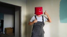 Arbeitskraft in der Uniform mit rotem Eimer auf seinem Kopf haben Spaß und Tanzen stock video