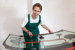Arbeitskraft in der Werkstatt des Glasers, die Dichtung für Windfang vorbereitet Lizenzfreies Stockbild