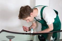 Arbeitskraft in der Werkstatt des Glasers, die Dichtung für Windfang vorbereitet Lizenzfreie Stockfotos