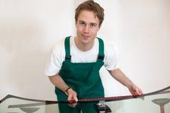Arbeitskraft in der Werkstatt des Glasers, die Dichtung für Windfang vorbereitet Stockbilder