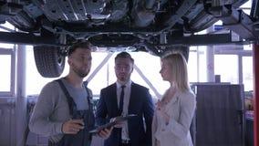 Arbeitskraft des Autoservices Frau und Mann mit Klemmbrett in den Händen konsultieren, die unter dem Automobil gehoben auf eine H stock video footage