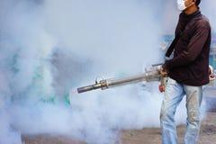 Arbeitskraft, die Abfluss am Wohngebiet mit Insektenvertilgungsmitteln zum ki einnebelt Stockfotos